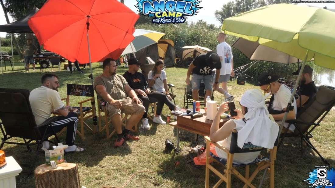 Mehrere Personen sitzen um ein Lagerfeuer in Campingstühlen.