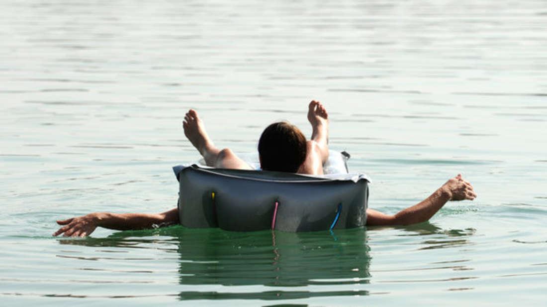 Ein Mann liegt auf einer Luftmatratze und lässt sich treiben (Symbolfoto).
