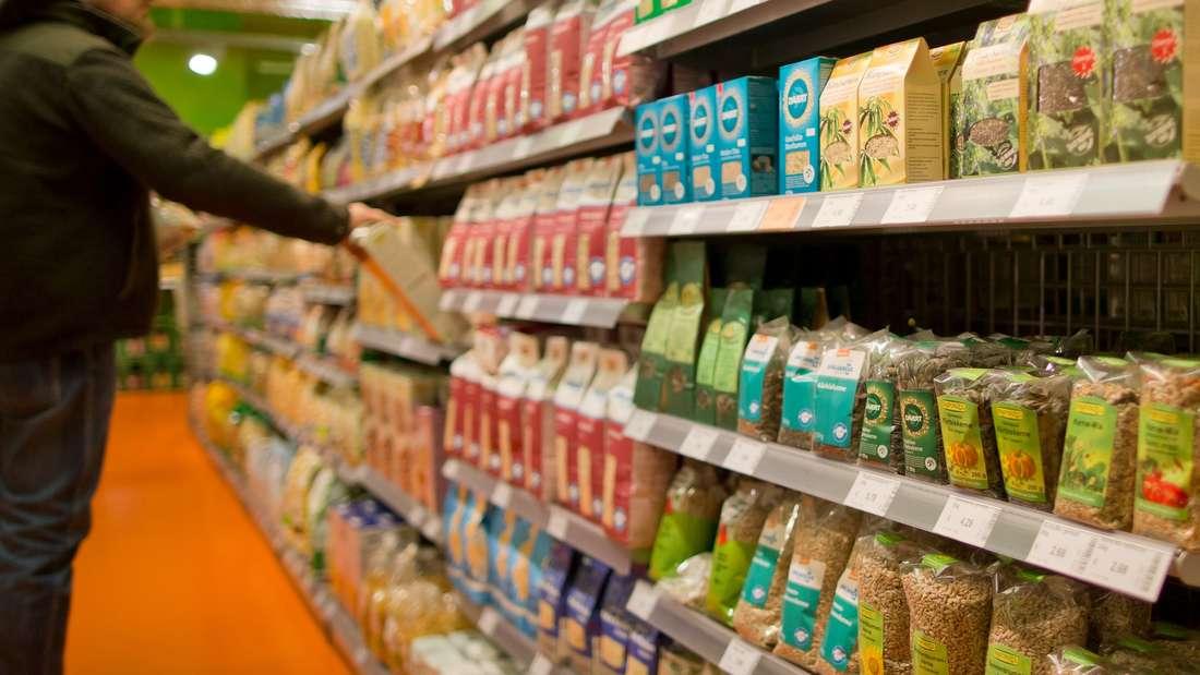 Ein Kunde greift nach ein Produkt in einem Regal in einem Supermarkt