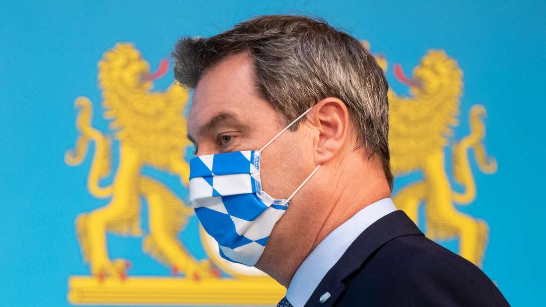 Markus Söder (CSU) mit einer blau-weiß karierten Corona-Schutzmaske in der Staatskanzlei in München