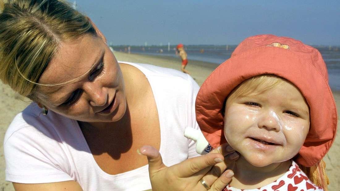 Rabea Herten aus Delmenhorst cremt ihre Tochter Leoni-Christin am Dienstag (20.08.2002) am Strand von Hooksiel (Kreis Friesland) mit Sonnencreme ein. Der bisher heißeste Augusttag in diesem Jahr fordet Sonnenmilch mit hohem Schutzfaktor. An der ostfriesischen Nordseeküste wurden Temperaturen von bis zu 30 Grad Celsius erreicht. (Symbolbild