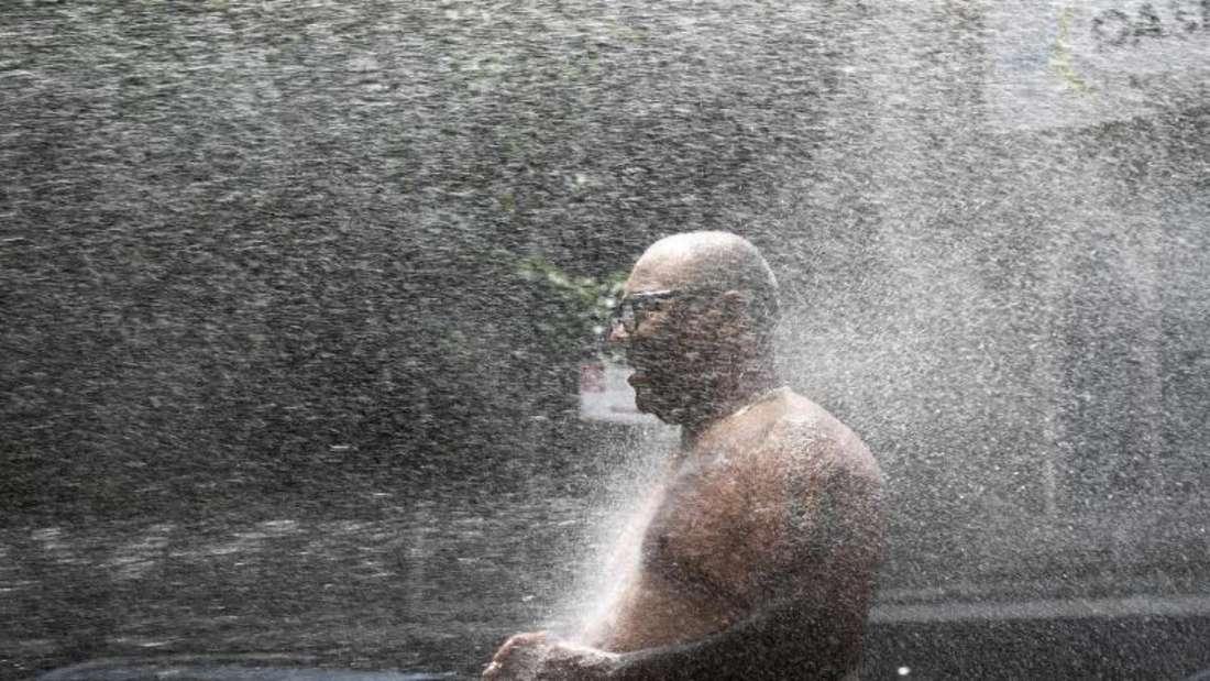 Rey Gomez kühlt sich in New York im Wasser eines Hydranten ab. Foto: Mark Lennihan/AP/dpa