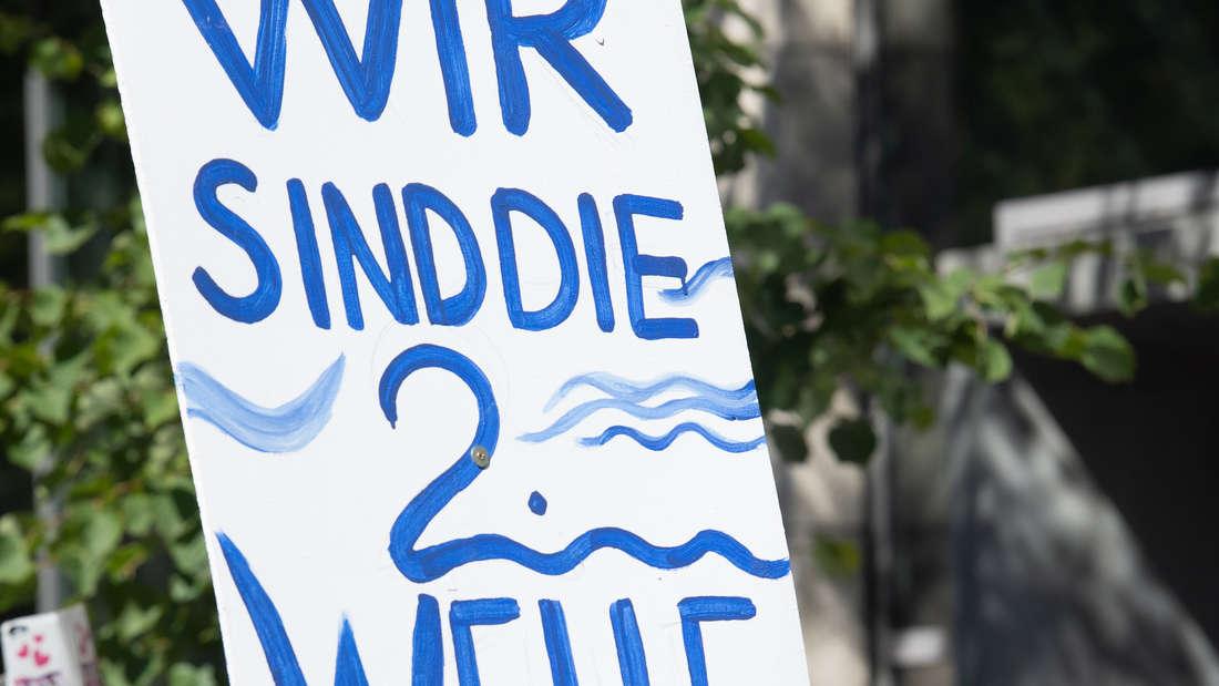 """Ein Schild mit der Aufschrift """"Wir sind die zweite Welle""""."""