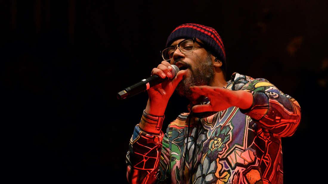 Rapper Sammy Deluxe singt auf einer Festival-Bühne in ein Mikrofon