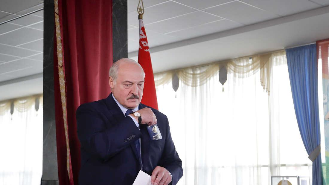 Amtsinhaber Alexander Lukaschenko mit seinem Stimmzettel bei der Wahl in Belarus in einem Wahllokal.
