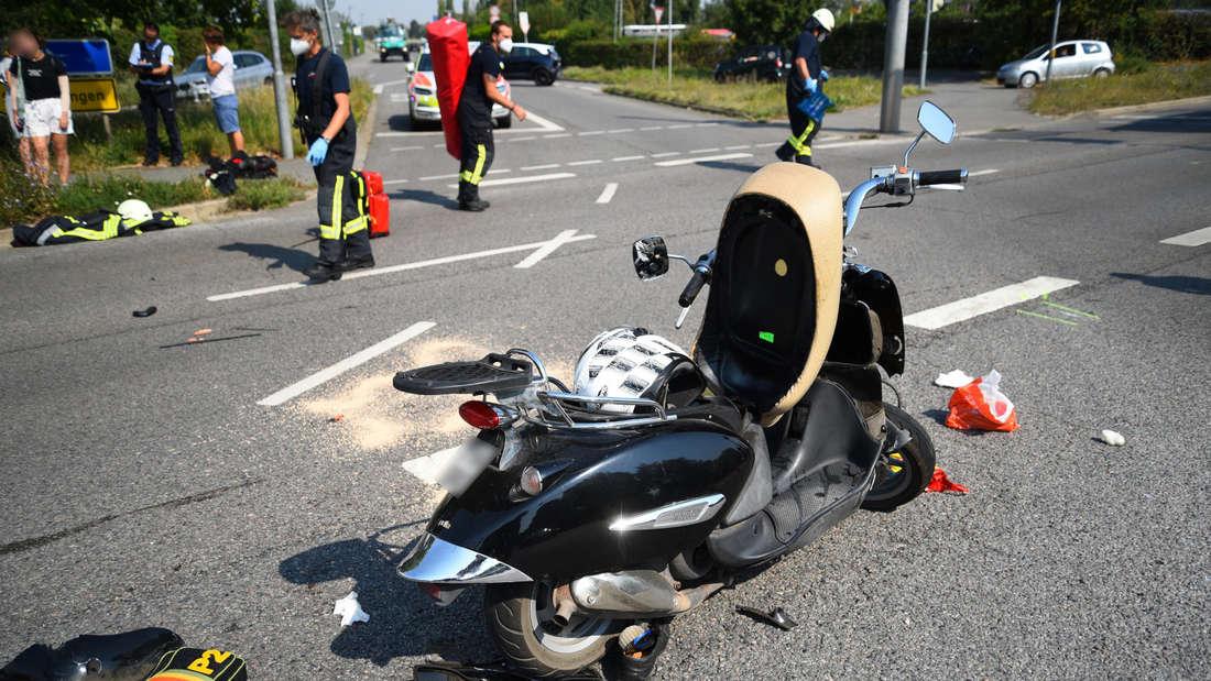 Ein zerstörter Roller auf einer Kreuzung, dahinter räumen Feuerwehrleute auf.