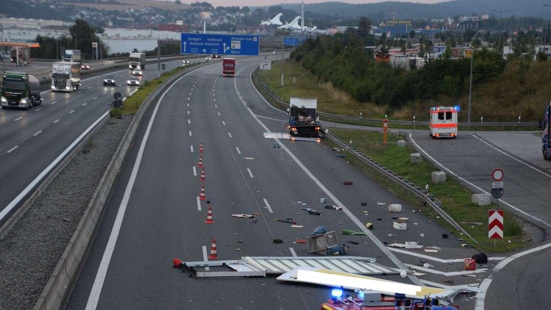 Ein kaputter Lkw auf der Autobahn. Dahinter liegen verschiedene Möbel.