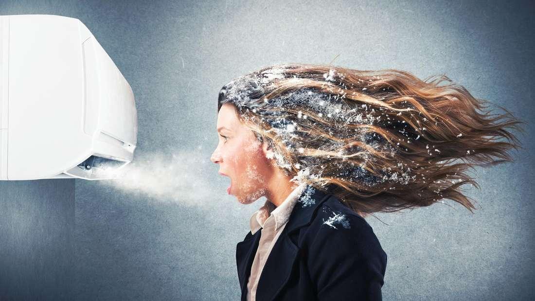 Eine Frau mit Frost in den Haaren steht vor einer Klimaanlage (Symbolfoto)