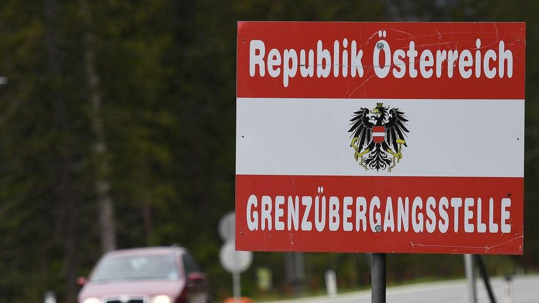 Ein Schild mit der Aufschrift Grenzübergangsstelle Österreich steht an einer Straße.