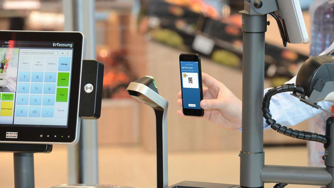 Ein Kunde hält sein Mobiltelefon mit der Lidl-Plus App an das Lesegerät an der Kasse.