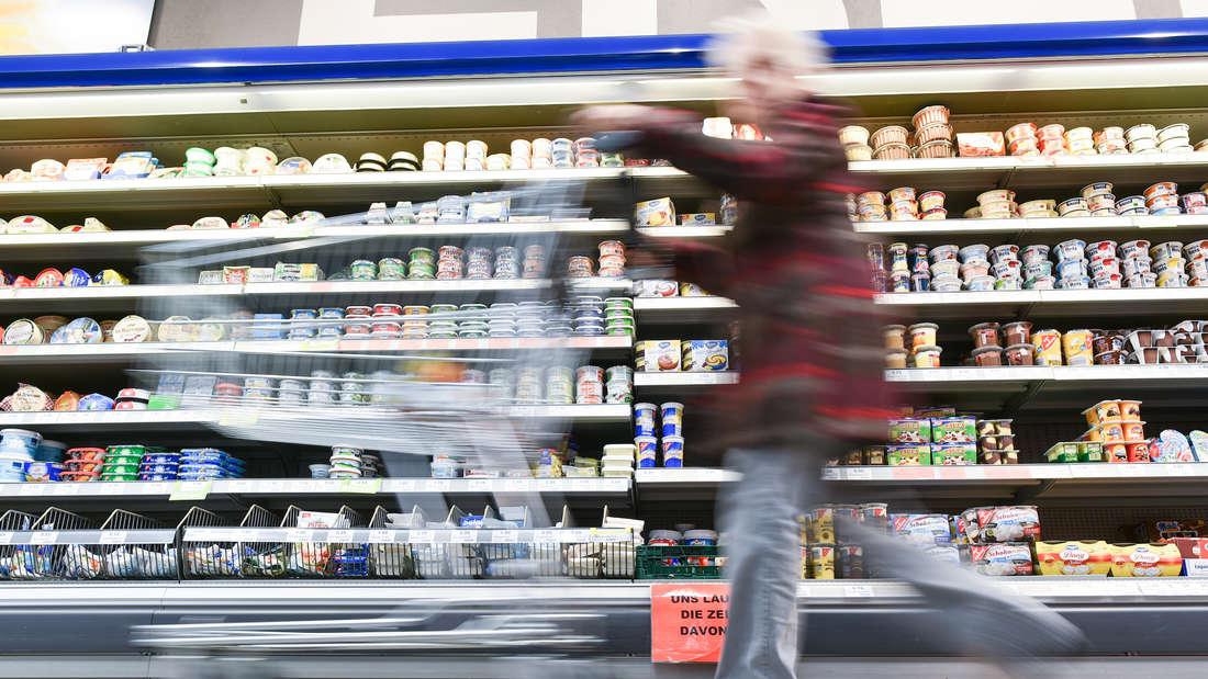 Eine Kundin geht in einem Supermarkt mit ihrem Einkaufswagen an einem Kühlregal vorbei.