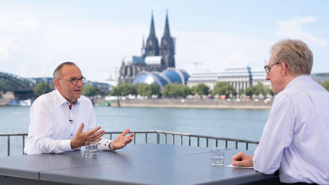 Norbert-Walter Borjans sitzt mit Theo Koll an einem Tisch. Im Hintergrund sieht man den Köllner Dom.