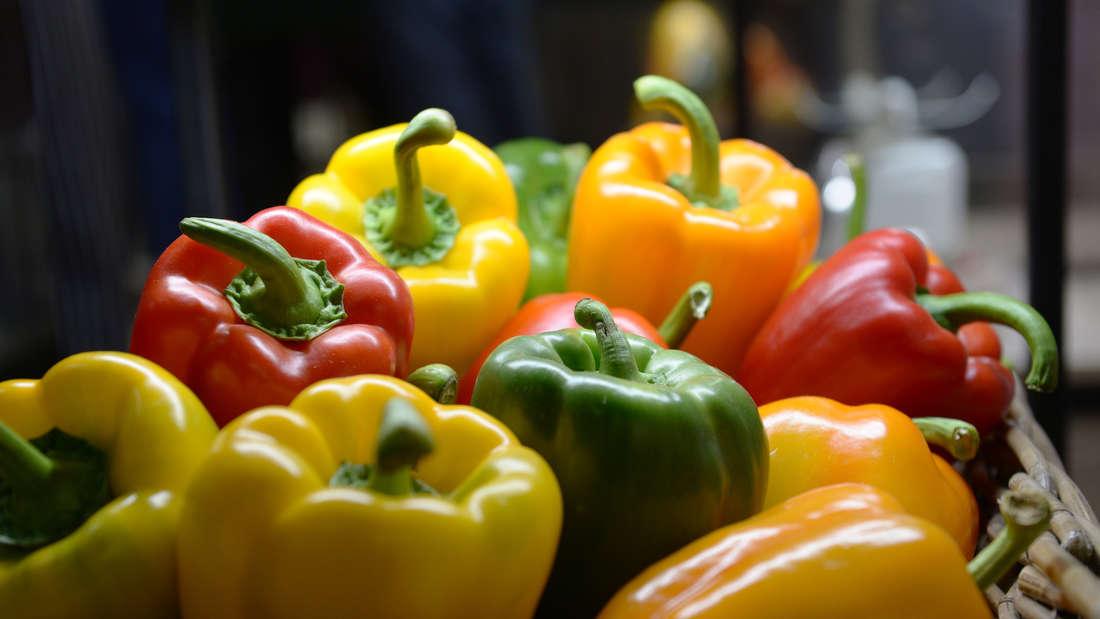 In einem Korb liegen grüne, rote, gelbe und orange Paprika.