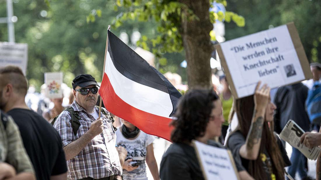 Ein Mann hält die Fahne des deutschen Kaiserreiches hoch.