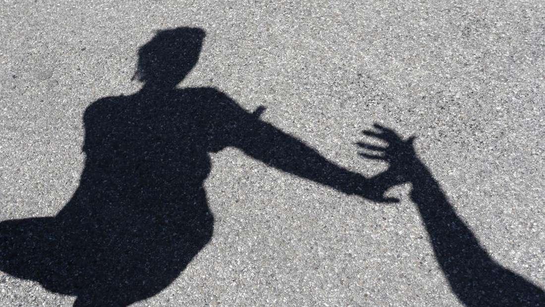 Der Schatten einer Frau, die auf der Straße angegriffen wird (Symbolfoto)