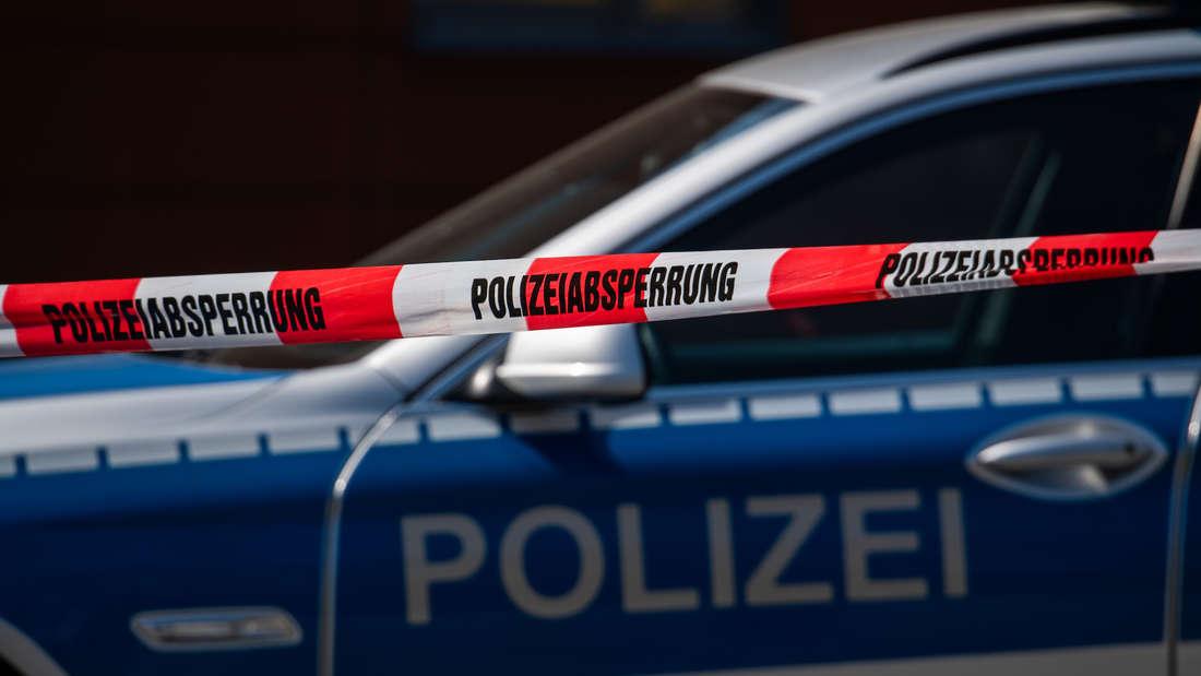 Ein Polizeiauto, davor ein Absperrband.