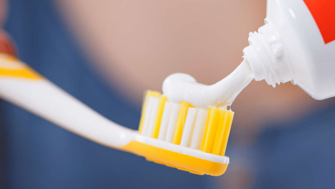Auf einen Zahnbürstenkopf wird Zahnpasta aufgetragen.