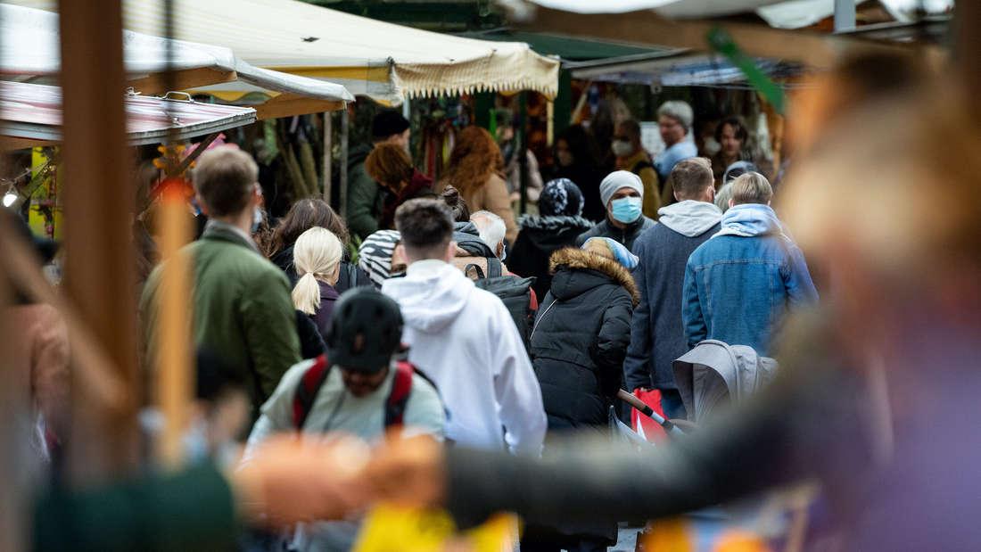 Mehrere Personen mit Masken laufen über einen Markt.