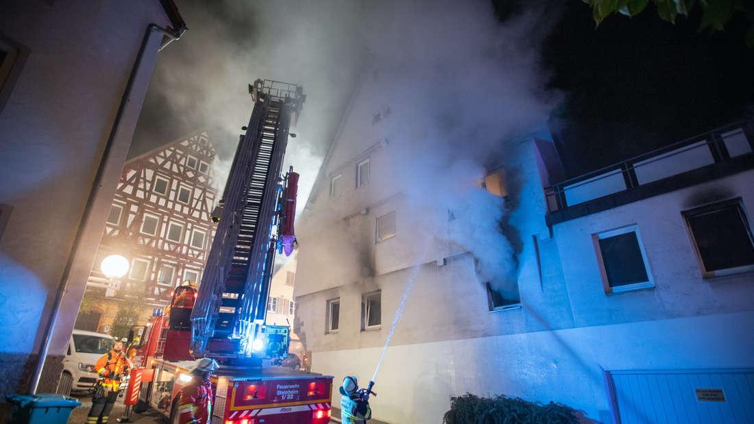 Feuerwehrleute löschen nach einem Brandanschlag einen Brand in einem Gebäude in der Innenstadt von Marbach.