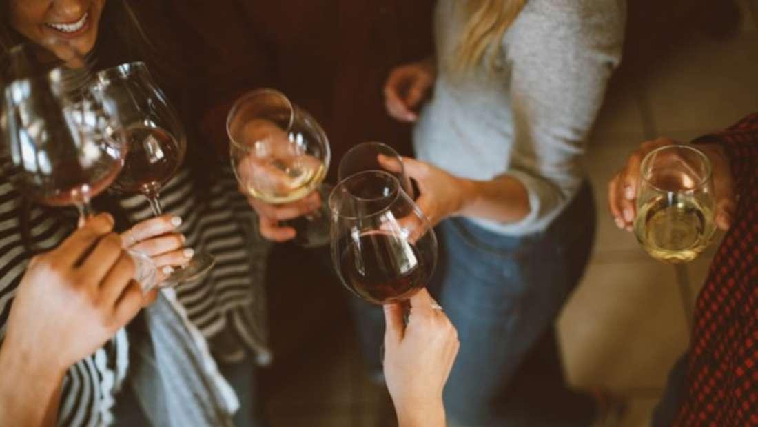 Mehrere Frauen stoßen mit Weingläsern an.