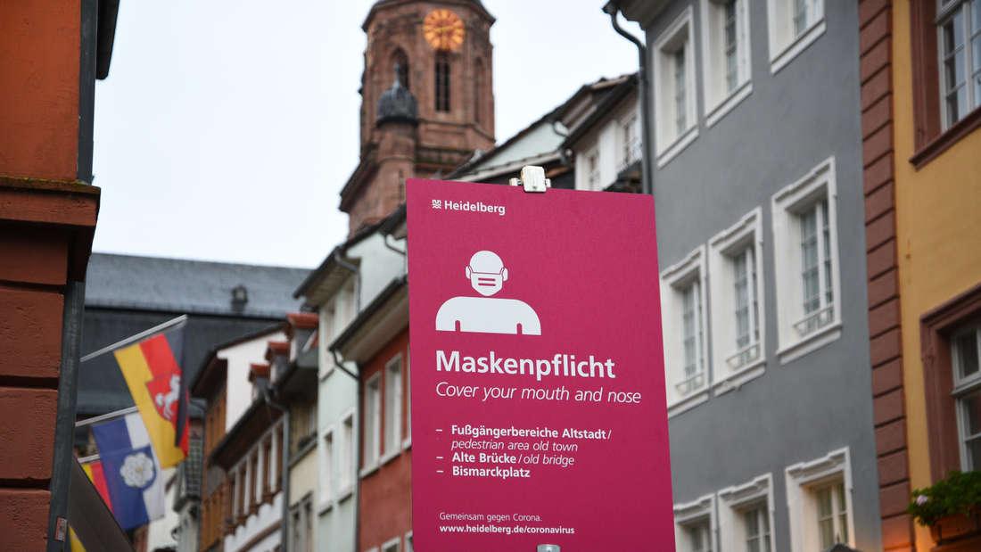 Ein Schild mit der Aufforderung Maskenpflicht, dahinter die Altstadt.