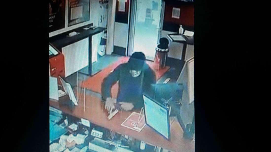 Der Räuber bedroht den Mitarbeiter mit einer Waffe.