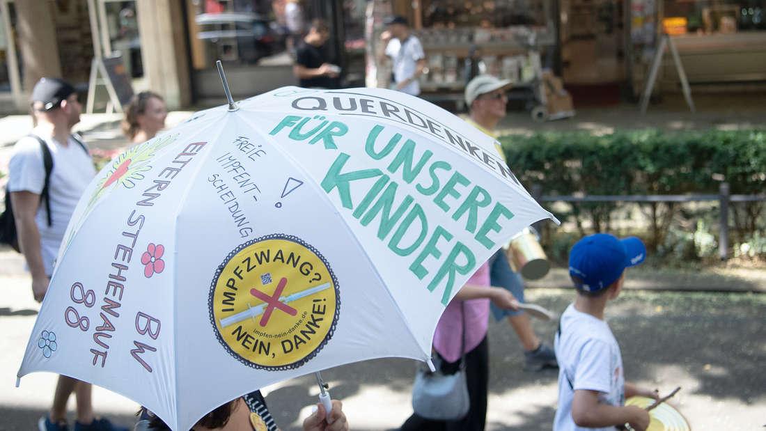 Eine Person mit einem Regenschirm. Darauf stehen Parolen.