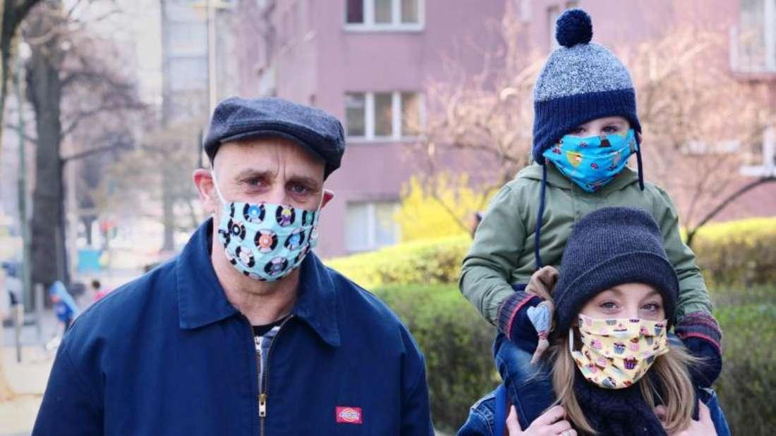 Eine Familie geht spazieren. Alle Familienmitglieder tragen dabei Masken, als Schutz gegen das Coronavirus. Foto: Wolfram Steinberg/dpa