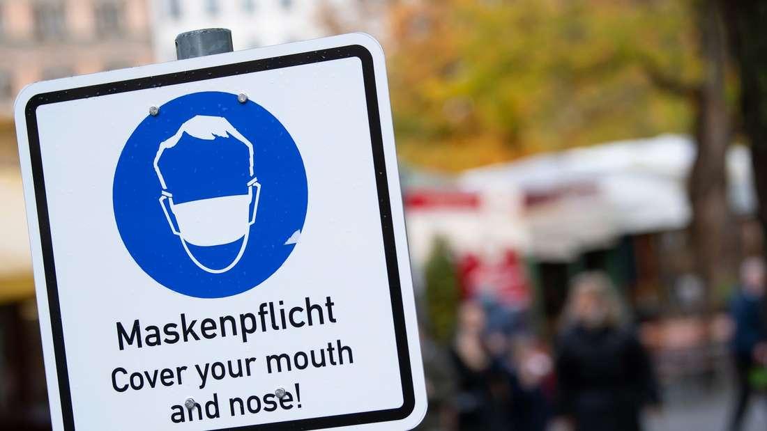 """Corona in München: Ein Hinweisschild mit der Aufschrift """"Maskenpflicht - Cover your mouth and nose!"""" steht auf dem Viktualienmarkt in der Innenstadt."""