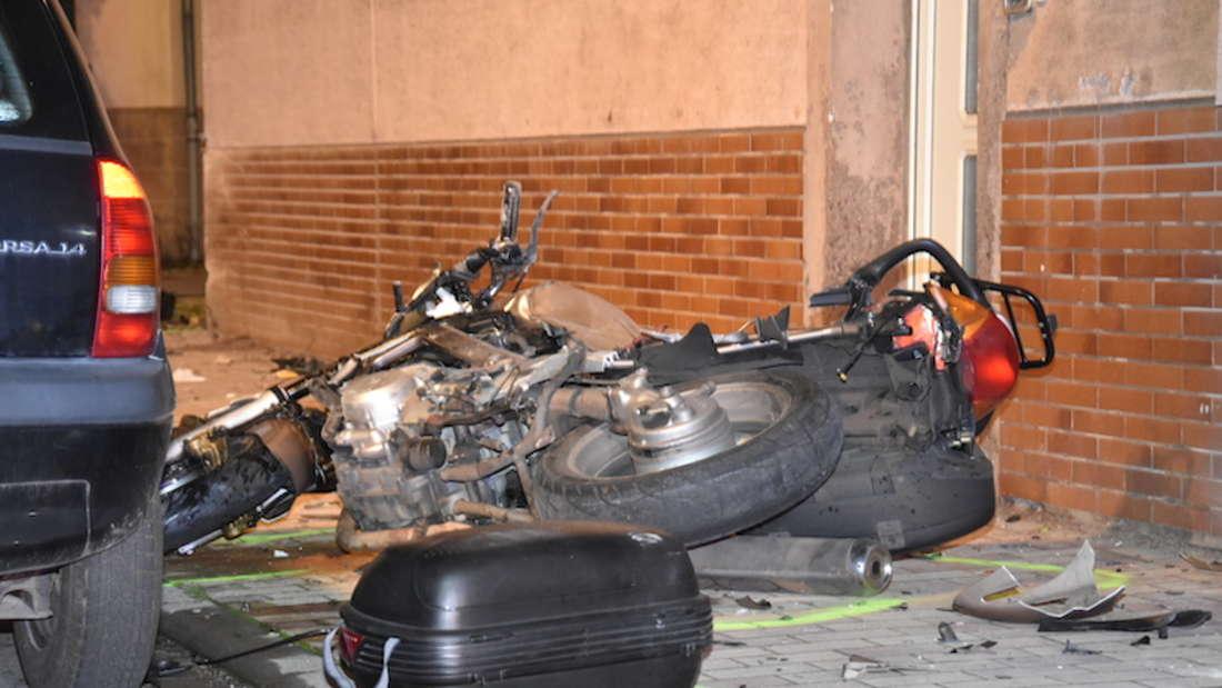 Ein Motorrad liegt an einer Hauswand am Boden.