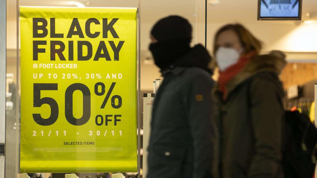 Werbung für den Aktionstag Black Friday hängt im Schaufenster eines Ladens in der Innenstadt. Davor gehen Passanten mit Mundschutzmasken entlang.