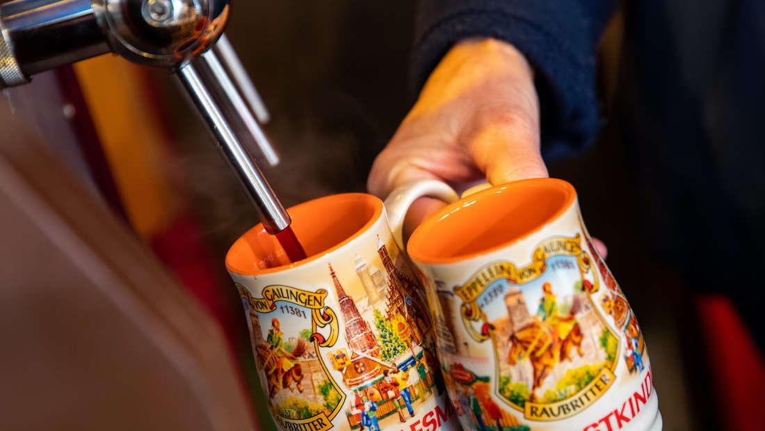 Zwei Tassen werden mit Glühwein befüllt.