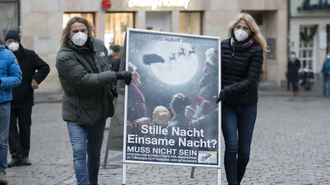 """Schlagersänger Dieter Thomas Kuhn und die Tübinger Notärztin Lisa Federle tragen ein Plakat mit der Aufschrift """"Stille Nacht Einsamme Nacht? Muss nicht sein"""" auf dem Rathausplatz in Tübingen."""