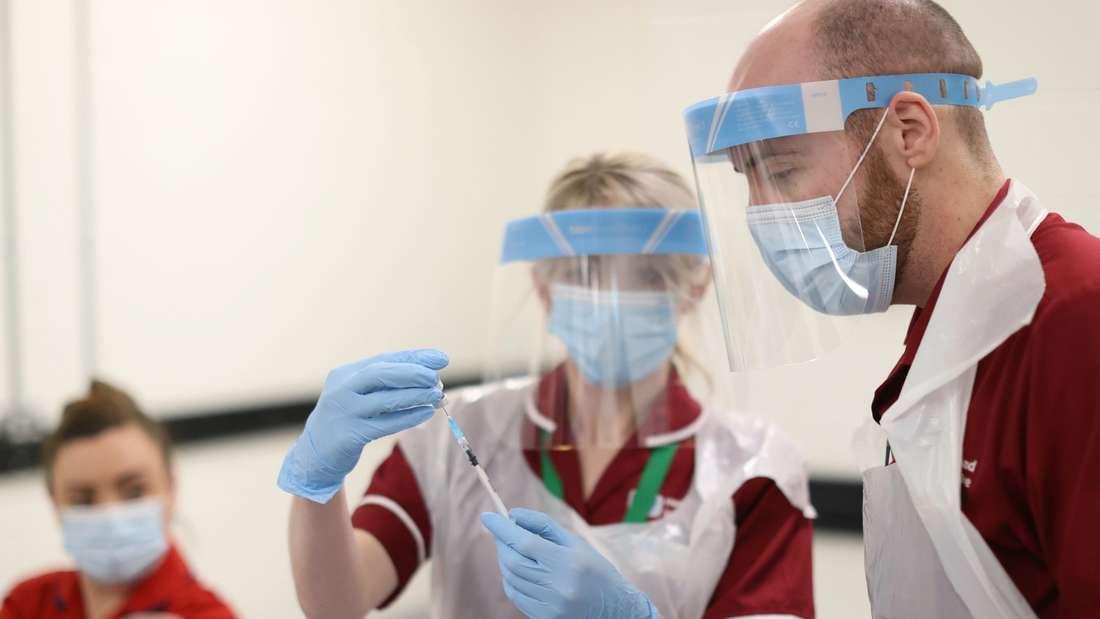 Medizinisches Personal bereitet eine Spritze mit Impfstoff gegen das Coronavirus vor.