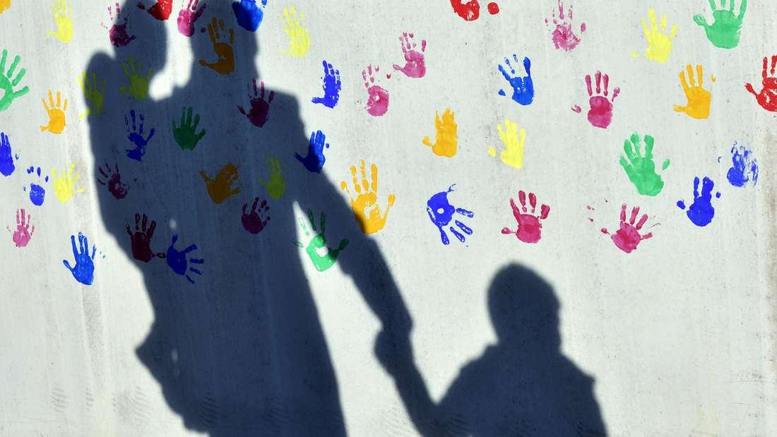 ARCHIV - Ein Mann mit einem Kind auf dem Arm und einem an der Hand wirft einen Schatten auf eine mit bunten Handabdrücken bemalte Wand einer Kindertagesstätte.