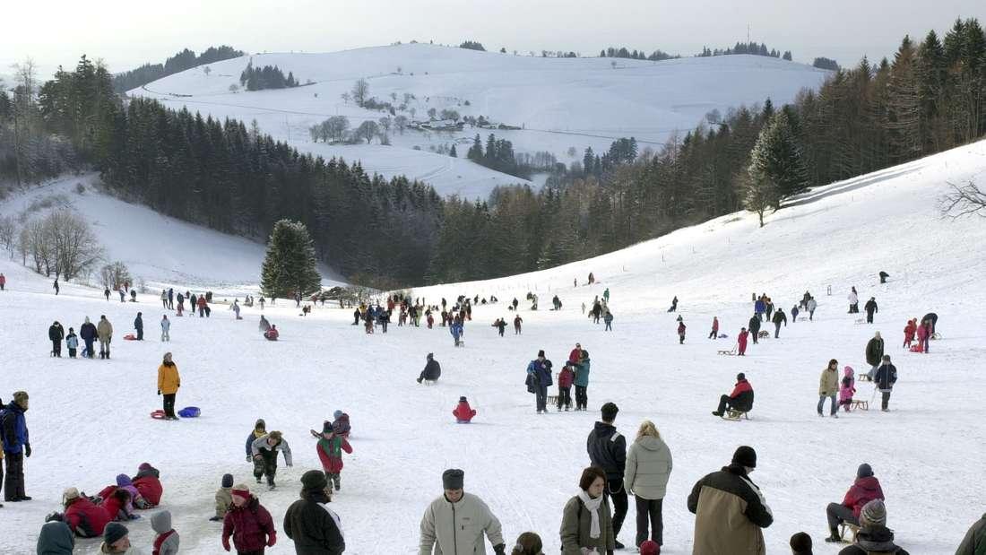 Viele Menschen fahren auf einem verschneiten Berg Schlitten.