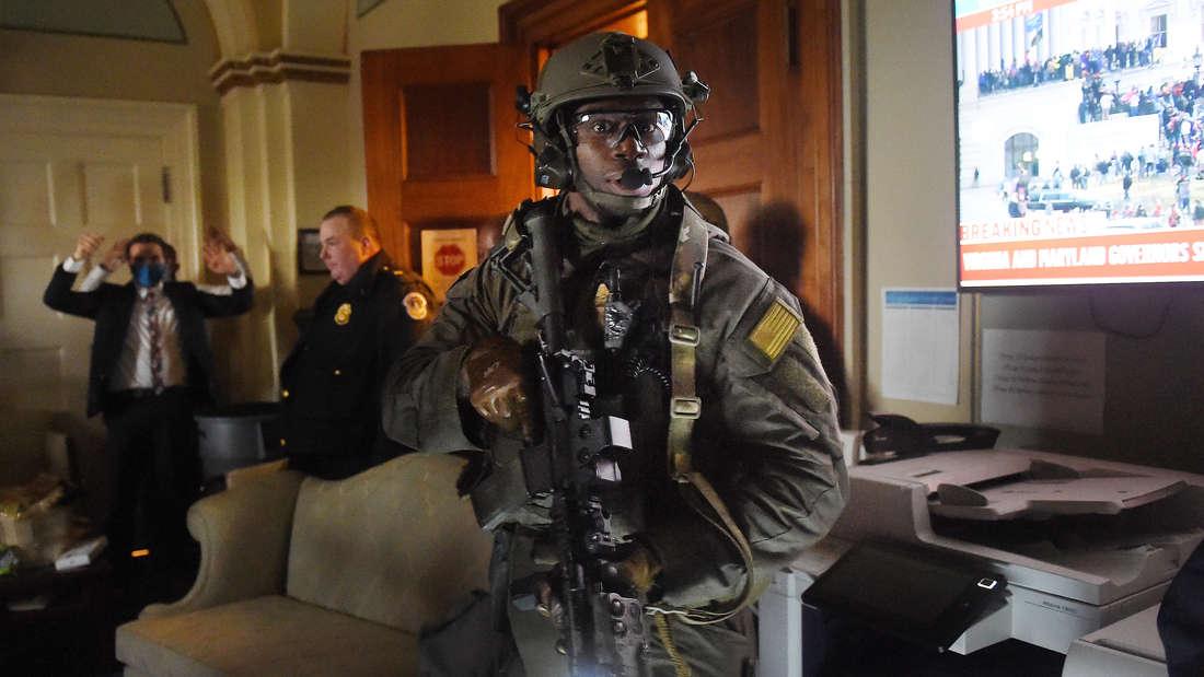 Ein einzelner, schwer bewaffneter Polizist sondiert die Lage innerhalb des Kapitols.
