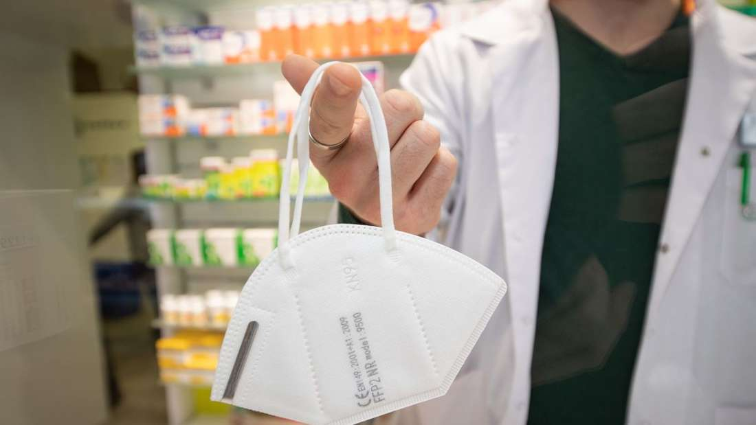 Ein Apotheker hält zur Illustration eine Mund- und Nasenschutzmaske an einem Finger.