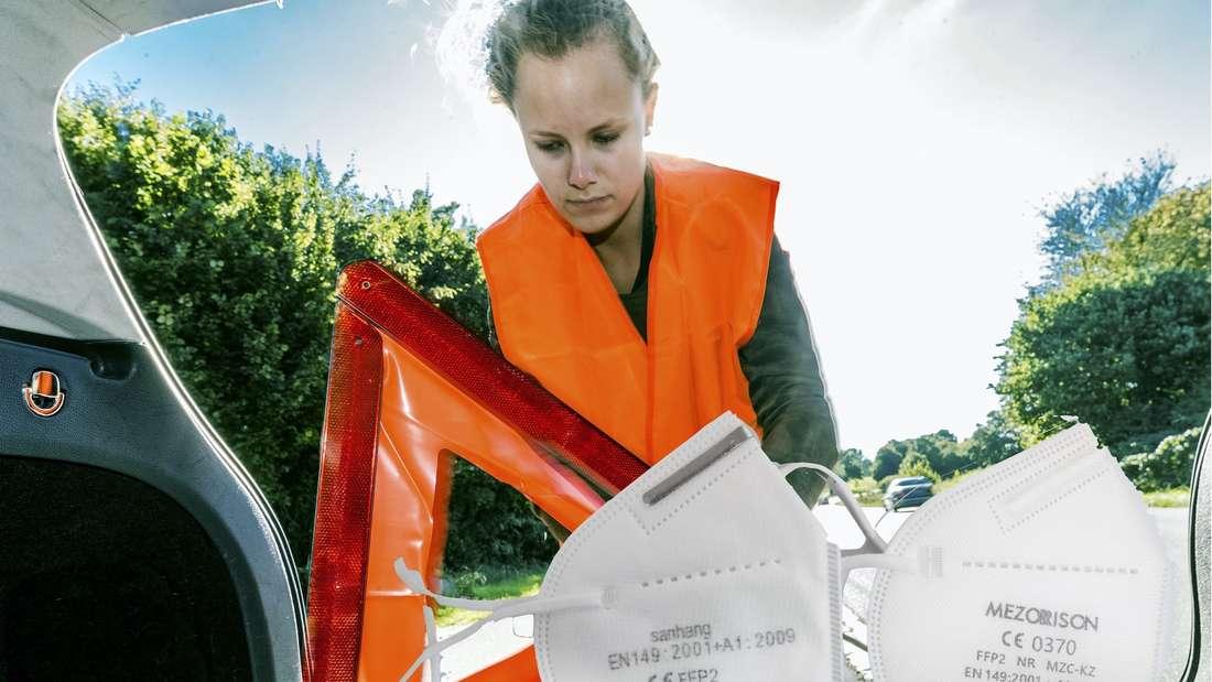 Eine Frau trägt eine Warnweste und holt ein Warndreieck aus dem Kofferraum.