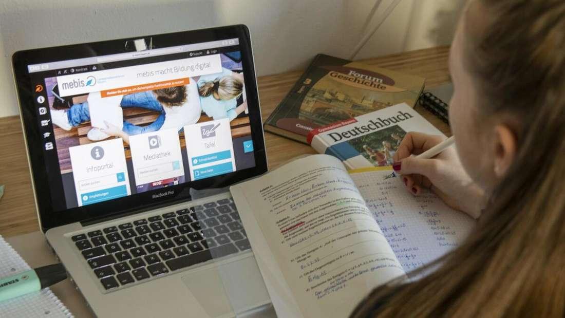 Ein Mädchen lernt am Computer für die Schule.