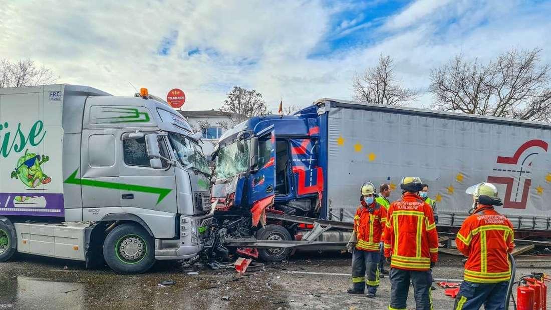 Zwei Lkw sind frontal zusammengekracht. Davor stehen Feuerwehrleute.