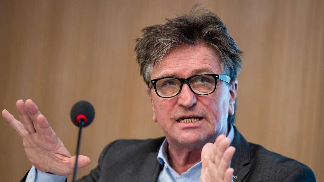 Manfred Lucha gestikuliert auf einer Pressekonferenz und spricht in ein Mikrofon.