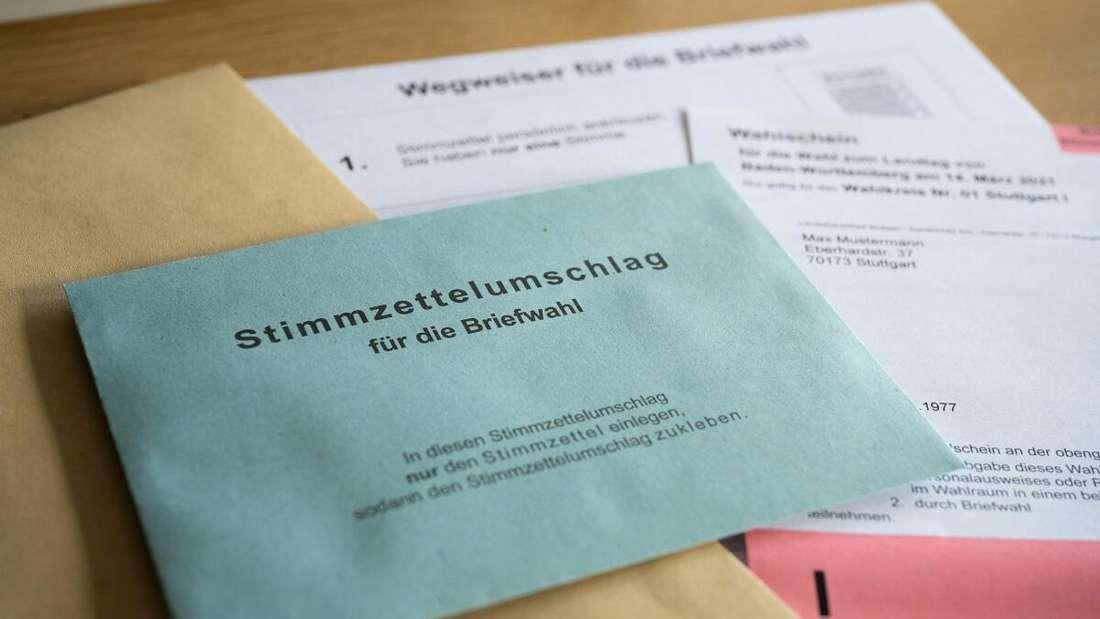 Ein Stimmzettelumschlag für die Briefwahl, darunter liegen ein Wahlschein und ein Wegweiser für die Briefwahl auf einem Tisch