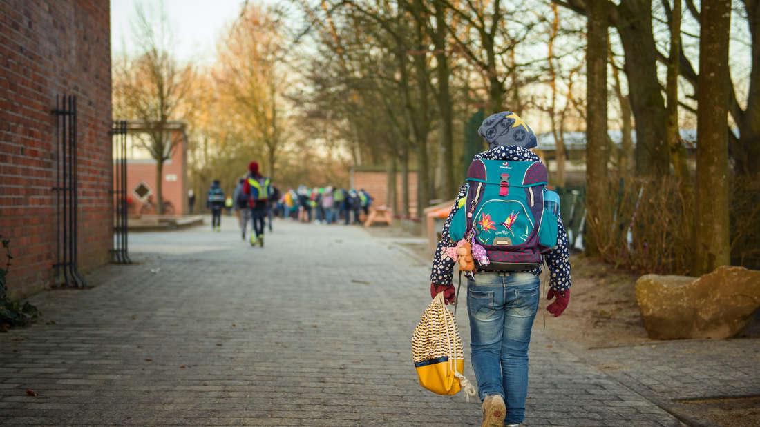 Ein Schulkind läuft auf einem Weg.