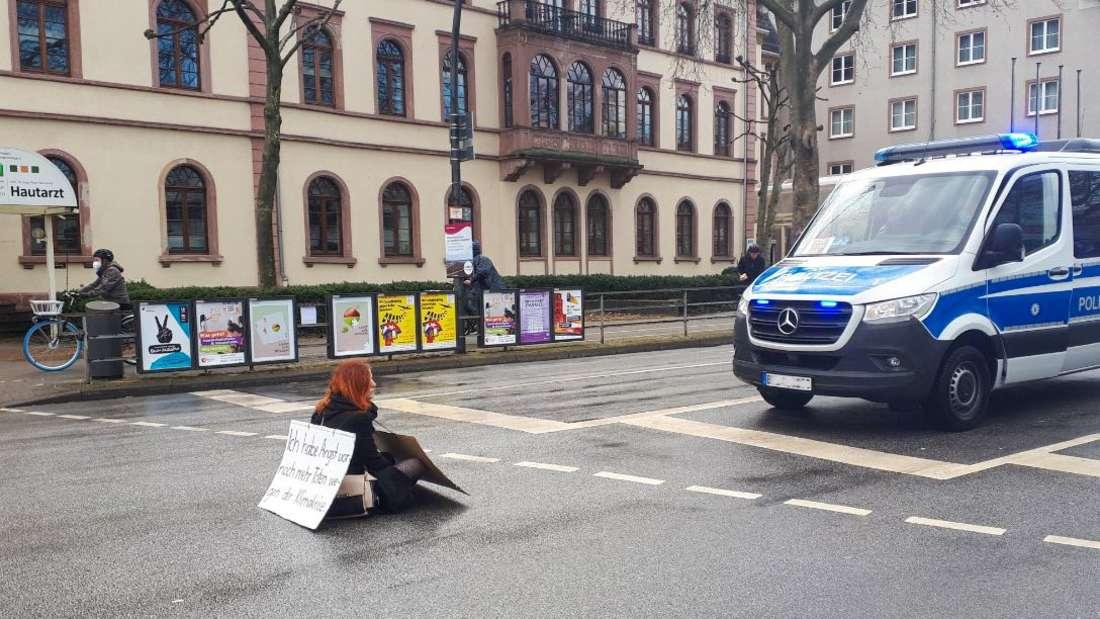 Heidelberg: Eine Extinction-Rebellion-Aktivistin blockiert den Verkehr am Römerkreis.