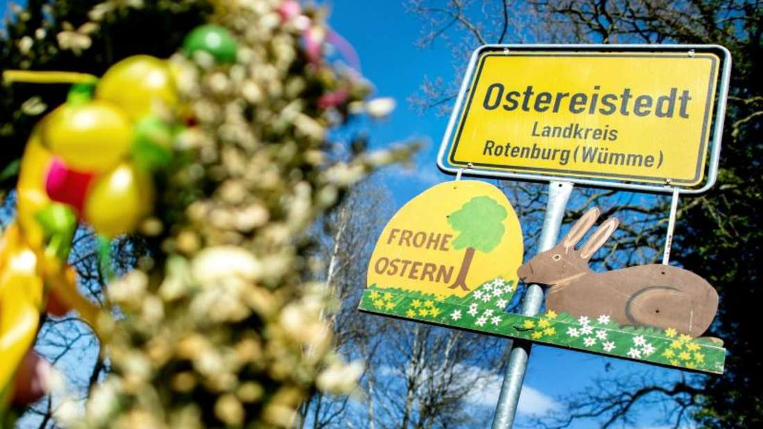 """Ein Schild mit der Aufschrift """"Frohe Ostern"""" hängt unter dem Ortsschild am Ortseingang von Ostereistedt."""