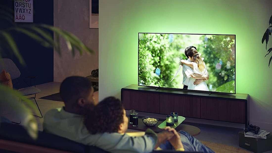 Zwei Männer sitzen Arm in Arm auf der Couch und schauen TV mit einem Philips Ambilight.