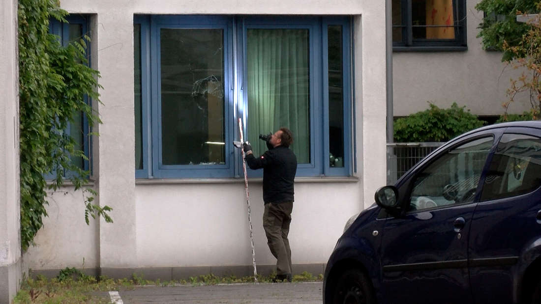 Ein Polizist fotografiert eine kaputte Fensterscheibe am Polizeirevier-Mitte in Heidelberg-Bergheim.