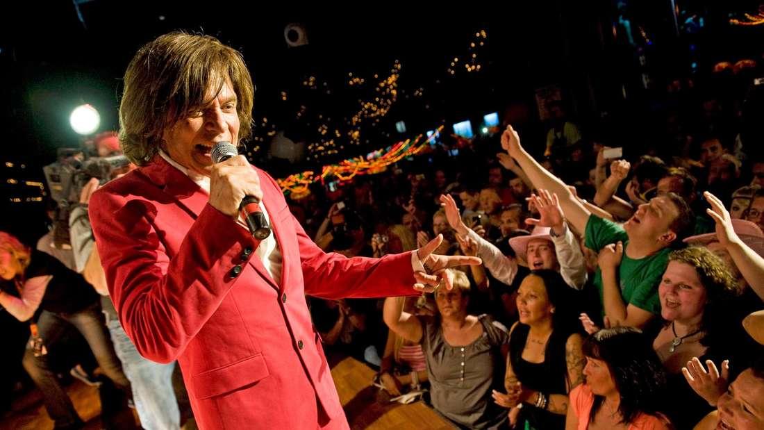 Jürgen Drews steht auf der Bühne im Mega-Park in einem roten Anzug