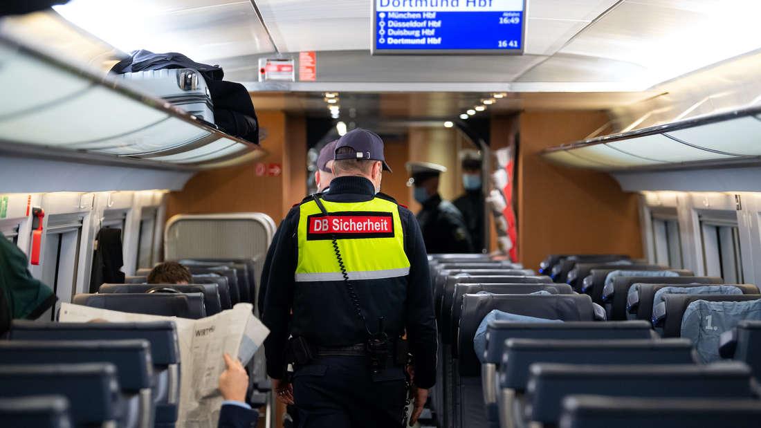 Ein Polizist kontrolliert in einem Zugabteil.